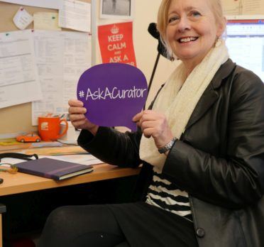 Image: woman in office holding purple sign