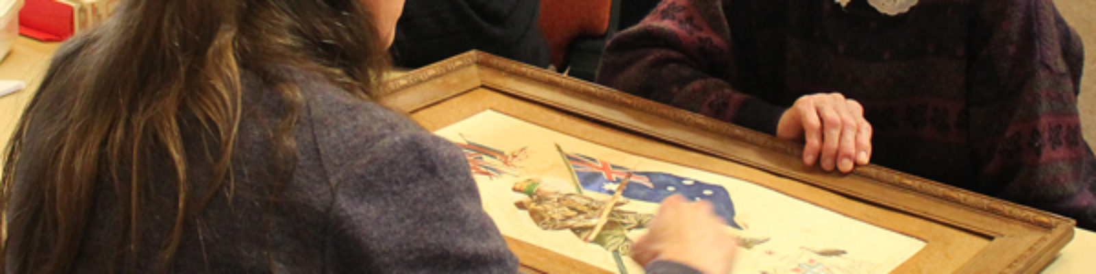 People around a table looking at a framed work.