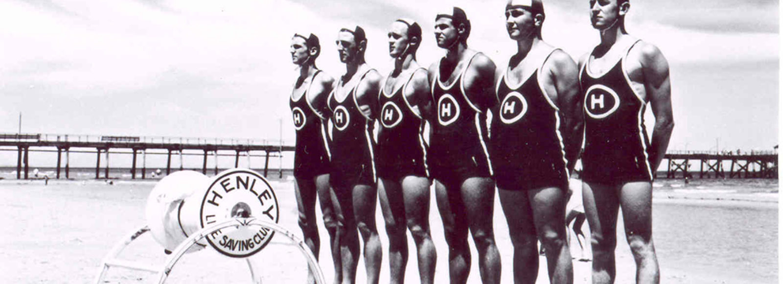 Image: six life savers standing in a row on a beach