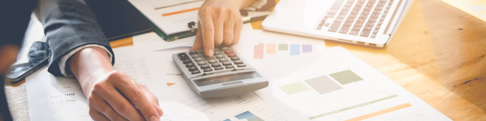 Person sitting at desk with a calculator looking at graphs.
