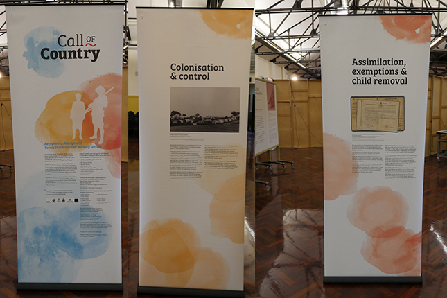 Collage of three banners on display in large hall.