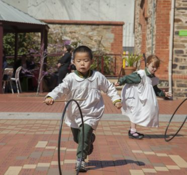 Young children running outside with hoops.