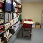 Storage area with shelves full of neatly stacked folders and other material