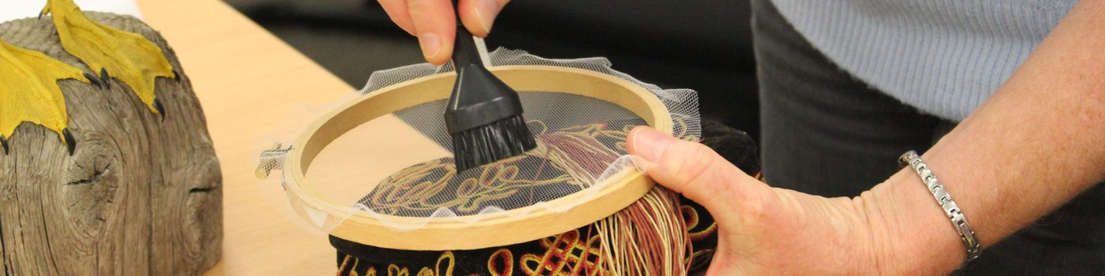 Pair of hands holding a small vacuum attachment on top of a gauze film over an embroidered cap.