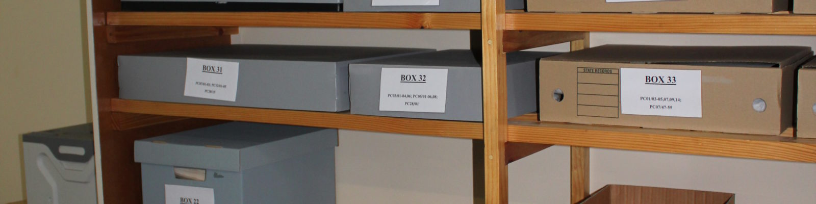 Shelves filled with grey archival boxes and brown cardboard boxes.