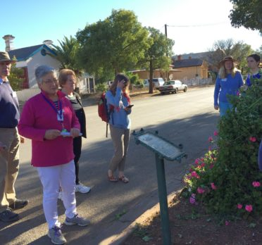Group of people standing around an interpretive sign on the side of a street. .
