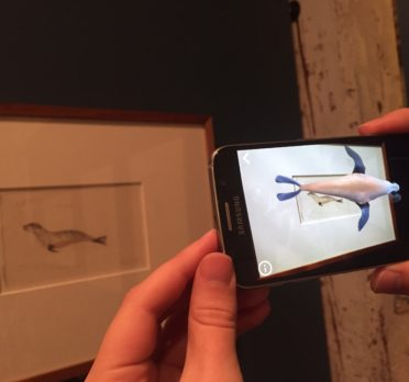 Hands holding a smart phone in front of an artwork with an animated seal appearing on the phone.