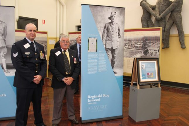 Men standing next to a pull up banner