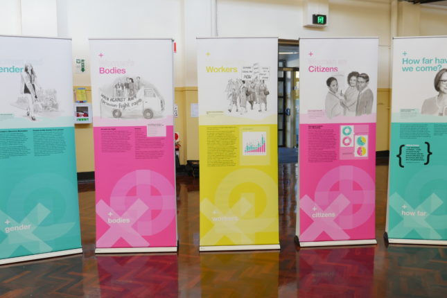 Row of five pull up banners in bright pink, aqua and yellow.