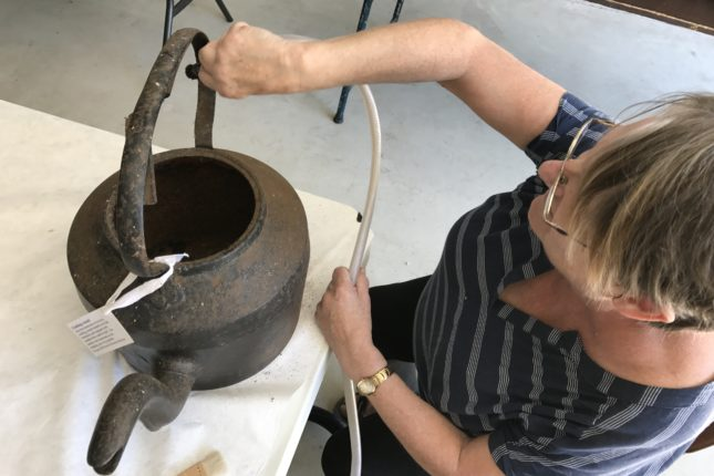 A woman with a vacuum cleaner brush attachment cleaning an old kettle.