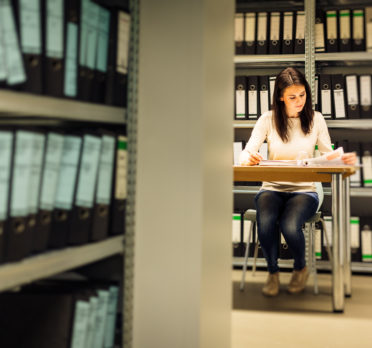 Young woman sitting at a desk surrounded by shelves of folders.