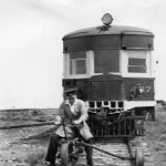 Man on a railway trike on tracks in front of a train.