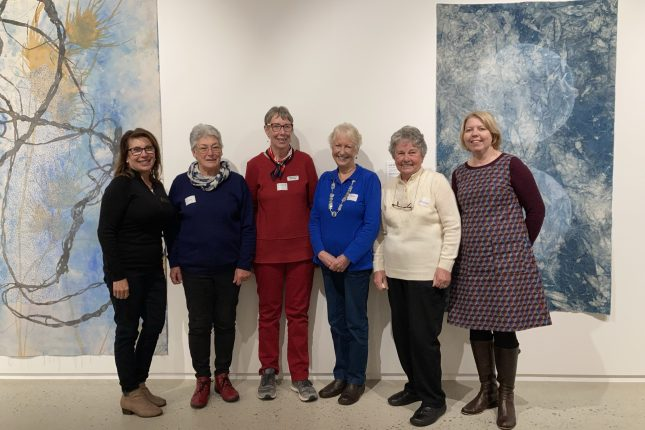 Group of smiling women in front of artworks in a gallery