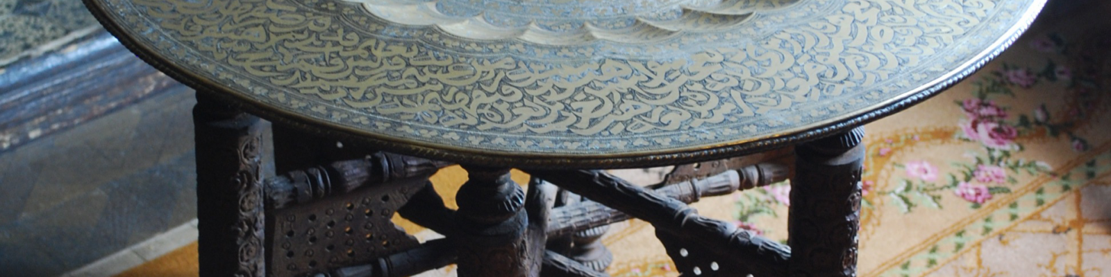 View looking down onto decorative metal tray round table top on carved wooden legs