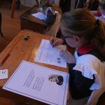 Child at old fashioned school desk writing with pen and ink