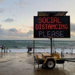 Digital sign reading 'Social Distancing Please'
