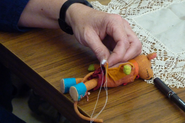 close up of hand holding needle and thread with a small soft toy