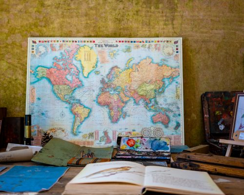 Map of the world sitting at the back of a cluttered desk covered in books and art materials.
