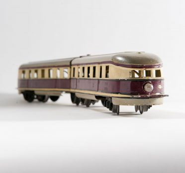 Toy tin train painted in a cream and brown stripe through the middle.
