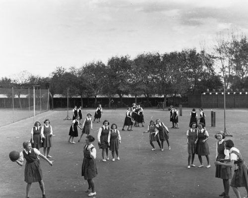 Group of girls in school uniform playing netball
